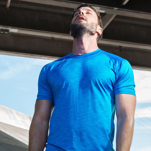 361° Plakate Beyond your expectations junger Mann in blauem Funktionsshirt blickt erschöpft nach oben