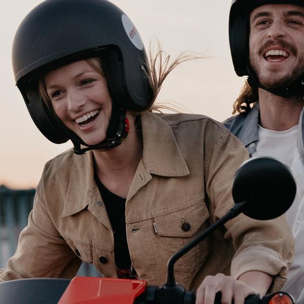 emmy Keyvisual zwei eine junge Frau und ein junger Mann fahren ausgelassen auf einem emmy Roller