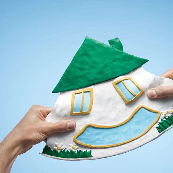 psd Bank Keyvisual ein Haus aus Knetgummi wird von zwei Händen in die breite gezogen, so dass die Fenster und die Tür ein lachendes Gesicht ergeben