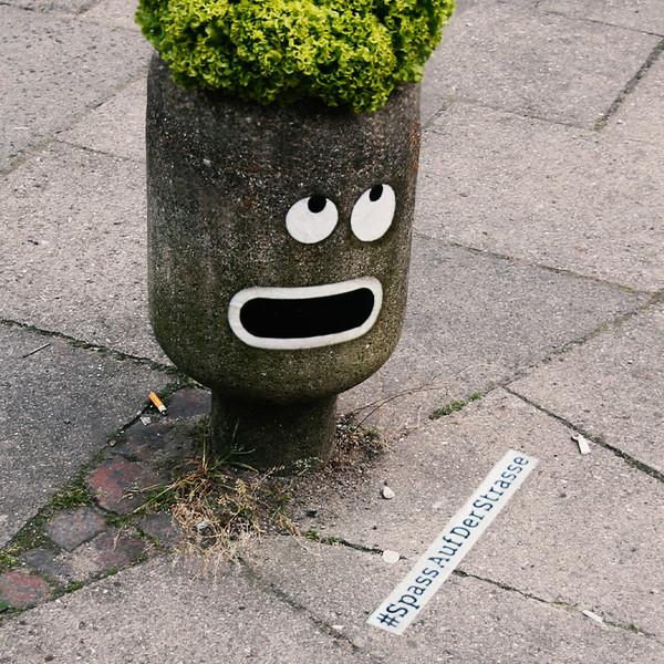 smart Pflanzkuebel mit Comic Augen und Mund, Hashtag auf der Strasse #SpassaufderStrasse