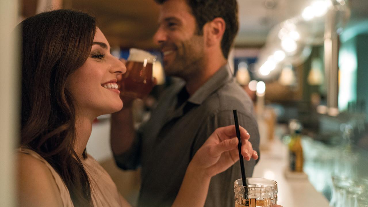 StrandGut Resorts lachendes junges Paar trinkt an einer Bar im StrandGut Resort in St. Peter-Ording