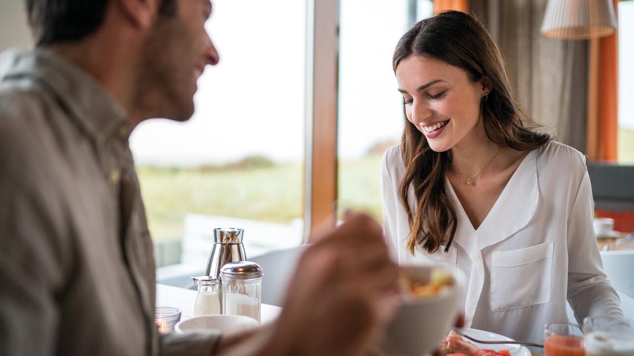 StrandGut Resorts glueckliches Paar frühstückt im StrandGut Resort in St. Peter-Ording