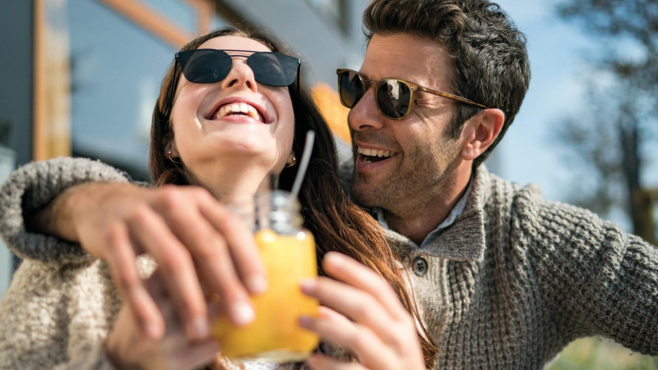 StrandGut Resorts junges Paar mit Sonnenbrillen lacht in herbstlichem Setting