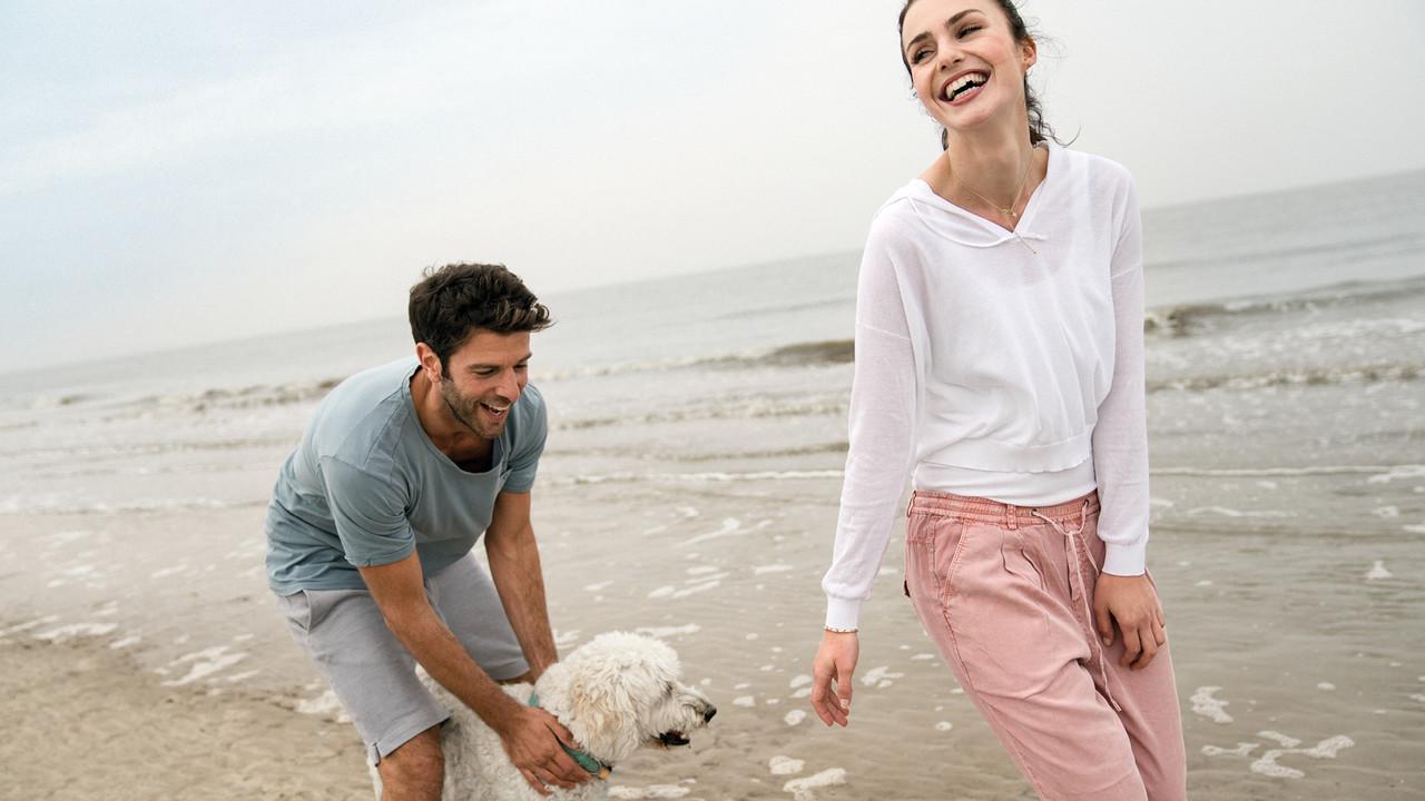 StrandGut Resorts junges Paar spielt mit ihrem Hund am Strand von St. Peter-Ording