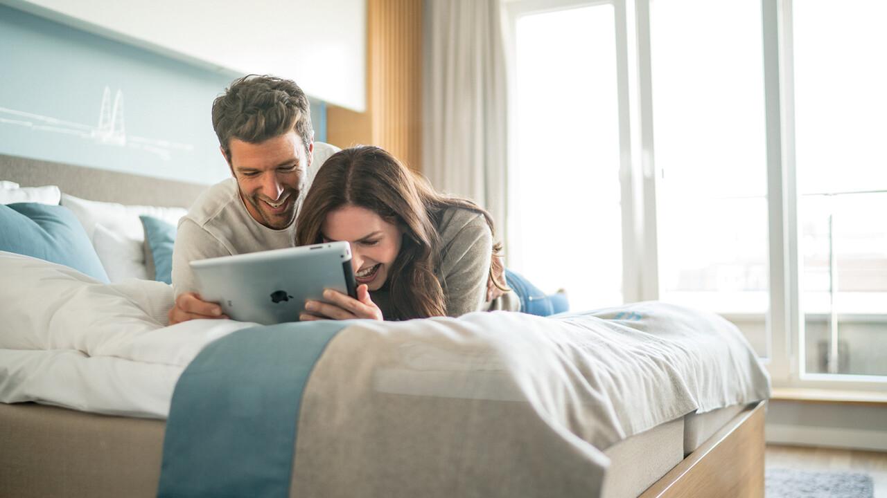 StrandGut Resorts junges Paar liegt lachend auf einem Bett und schaut auf ein Ipad