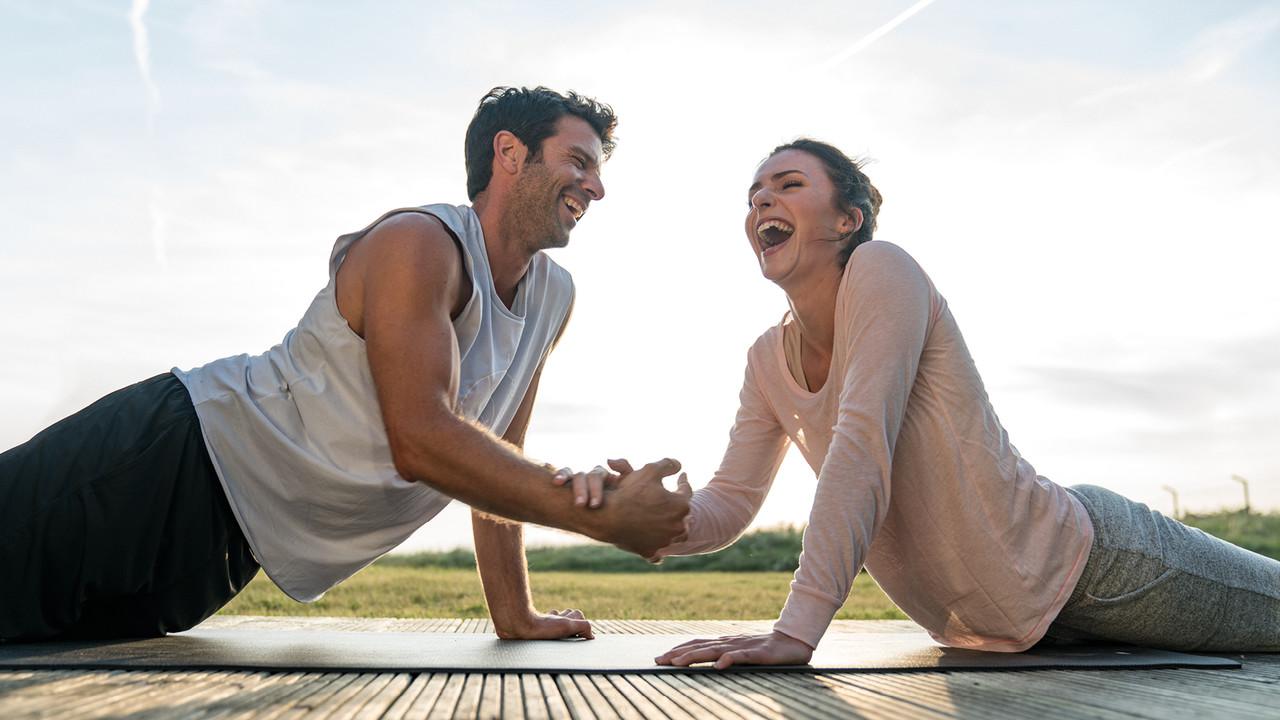 StrandGut Resorts junges Paar liegt in Yoga Pose lachend zusammen auf einer Matte