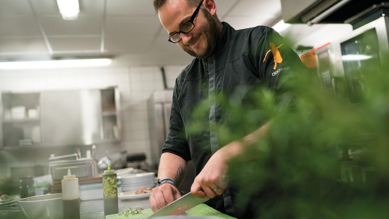 StrandGut Resorts lachender Koch schneidet Gemüse in der Kueche