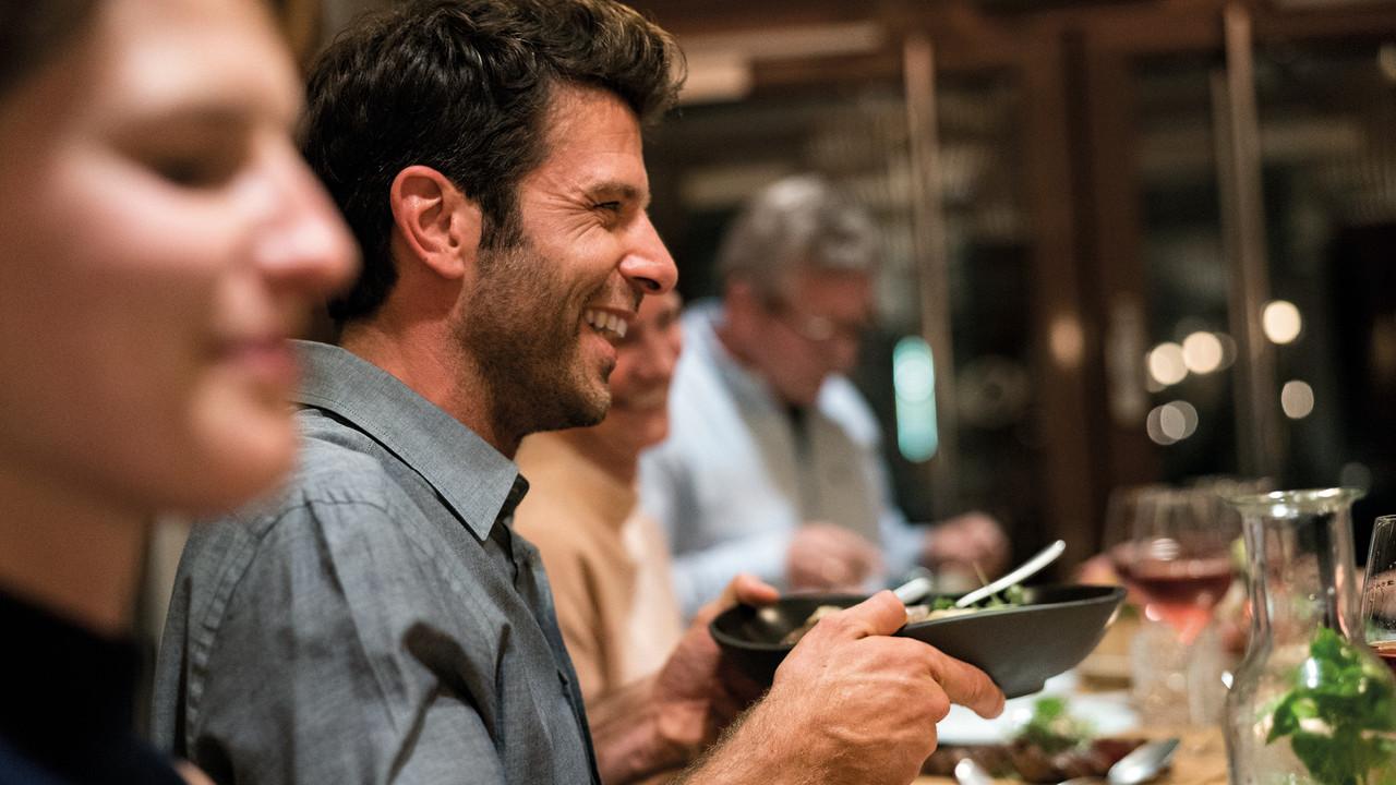 StrandGut Resorts glueckliche Gaeste essen im StrandGut Resort in St. Peter-Ording zu Abend, junger Mann haelt Salatschale
