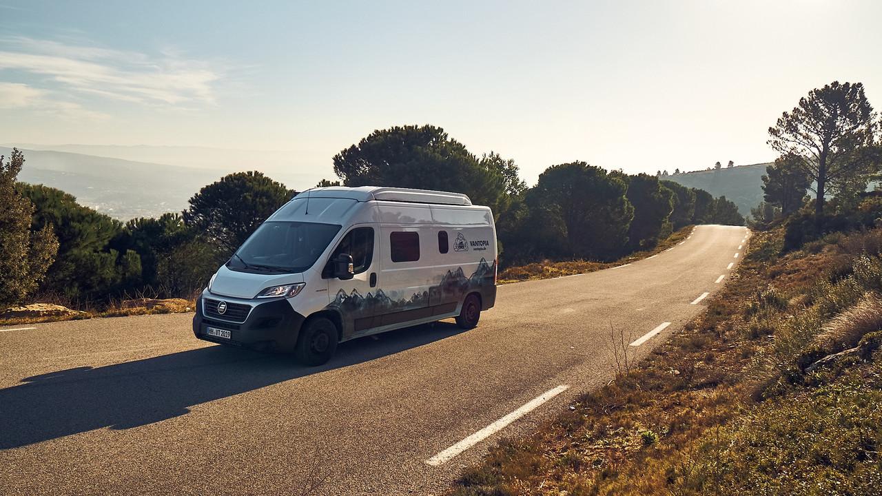 Vantopia Traveler Van von vorn auf einer Straße im Gruenen