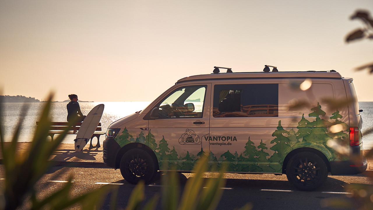 Vantopia Dreamer Van mit Frau im Neoprenanzug und Surfbrett auf einer Bank am Strand