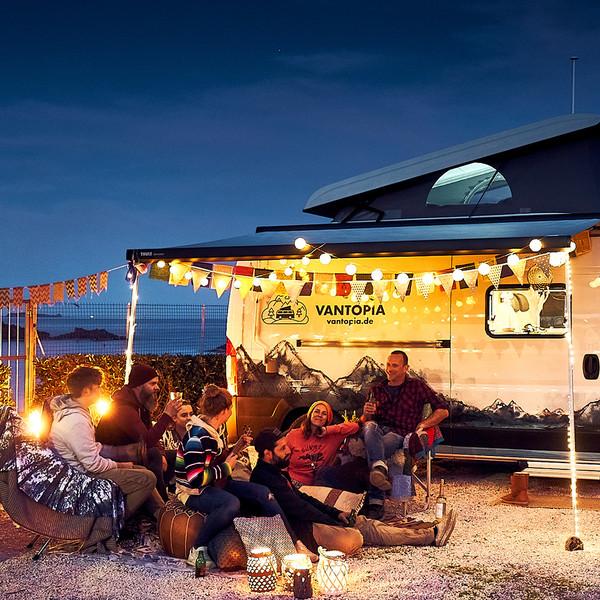 Vantopia Camping Vans Keyvisual Vans am Strand mit Lichteketten und jungen Urlaubern die gemeinsam die Nacht genießen