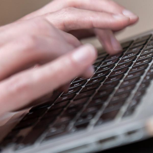 weibliche Haende die auf einem Macbook Air tippen