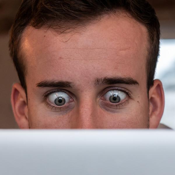 Mann schaut mit weit geoeffneten Augen auf ein Laptop Bildschirm